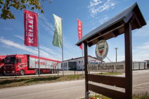 Das Ortsschild der Gemeinde Geslau. Im Hintergrund das Gebäude und Fahrzeuge der Firma Keitel