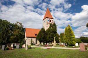 Die Kirche in der Gemeinde Neusitz mit dem Friedhof im Vordergrund