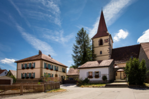 Die Kirche mit Spitzdach und das Pfarramt in der Gemeinde Ohrenbach
